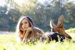 Härlig ung kvinna som ligger på gräs Royaltyfri Fotografi
