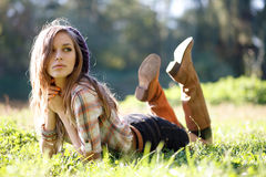 Härlig ung kvinna som ligger på gräs Royaltyfria Bilder