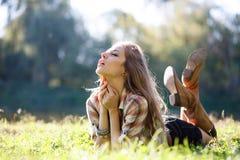 Härlig ung kvinna som ligger på gräs Arkivfoto