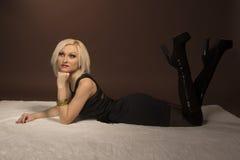 Härlig ung kvinna som ligger på vit matta Royaltyfria Bilder