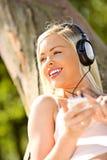 Härlig ung kvinna som lyssnar till hennes spelare mp3 Arkivbild