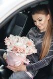 Härlig ung kvinna som mycket sitter på förarsätet i en bil med en rosa ask av mjukt, vitt, med en rosa list av tult-sänkan arkivfoto