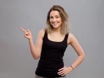 Härlig ung kvinna som pekar till någonstans royaltyfria foton