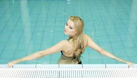Härlig ung kvinna som plattforer i en simbassäng royaltyfri bild