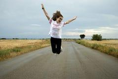 Härlig ung kvinna som poserar i en väg mellan två vetefält molnig dag Rödhårigt tonåring arkivfoto