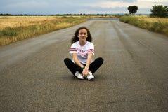 Härlig ung kvinna som poserar i en väg mellan två vetefält molnig dag Rödhårigt tonåring fotografering för bildbyråer