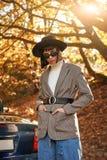 Härlig ung kvinna som poserar nära cabrioleten säsong för bana för höstfallskog royaltyfri foto