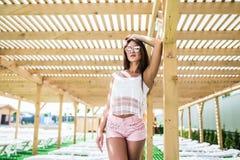 Härlig ung kvinna som poserar på chaisevardagsrummet nära simbassäng Arkivbild