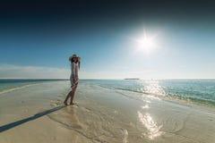 Härlig ung kvinna som poserar på den vita stranden, härligt landskap med kvinnan i Maldiverna, tropiskt paradis arkivfoto