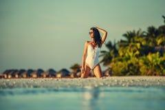Härlig ung kvinna som poserar på den vita stranden, härligt landskap med kvinnan i Maldiverna, tropiskt paradis royaltyfria bilder