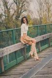 Härlig ung kvinna som poserar på en bro Fotografering för Bildbyråer