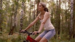 Härlig ung kvinna som rider ner skogvägen på en solig dag stock video