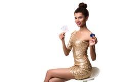 Härlig ung kvinna som rymmer överdängare två av kort och två chiper i hennes hand som isoleras på vit Royaltyfria Bilder