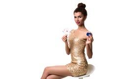 Härlig ung kvinna som rymmer överdängare två av kort och två chiper i hennes hand som isoleras på vit Arkivfoton