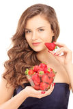 Härlig ung kvinna som rymmer en bunke av jordgubbar Royaltyfri Bild