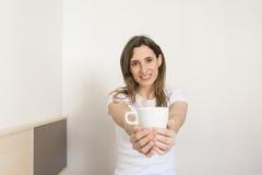 Härlig ung kvinna som rymmer en kopp kaffe i hennes sovrum Si Royaltyfria Foton
