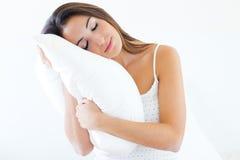 Härlig ung kvinna som rymmer en kudde och slepping på säng royaltyfri foto
