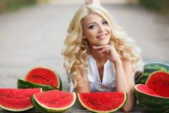 Härlig ung kvinna som rymmer en skiva av den mogna vattenmelon fotografering för bildbyråer