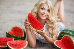 Härlig ung kvinna som rymmer en skiva av den mogna vattenmelon royaltyfri foto