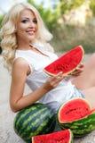 Härlig ung kvinna som rymmer en skiva av den mogna vattenmelon royaltyfri bild