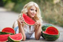 Härlig ung kvinna som rymmer en skiva av den mogna vattenmelon royaltyfri fotografi