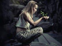 Härlig ung kvinna som rymmer en växt Royaltyfri Bild