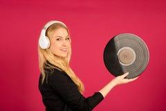 Härlig ung kvinna som rymmer en vinyl i henne händer, som hon lyssnar Fotografering för Bildbyråer