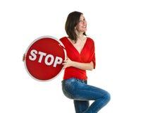 Härlig ung kvinna som rymmer ett stopptecken Arkivfoto