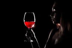 Härlig ung kvinna som rymmer exponeringsglaset av ett rött vin Royaltyfri Foto