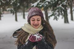 Härlig ung kvinna som rymmer insnöade tumvanten och att skratta fotografering för bildbyråer