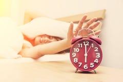 Härlig ung kvinna som rynkar pannan i säng- och innehavhand på röd al Royaltyfri Foto