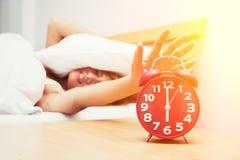 Härlig ung kvinna som rynkar pannan i säng- och innehavhand på röd al Royaltyfria Bilder