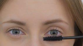 Härlig ung kvinna som sätter mascara Arkivfoton