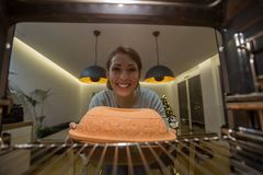 Härlig ung kvinna som sätter något i ugnen att laga mat arkivfoton
