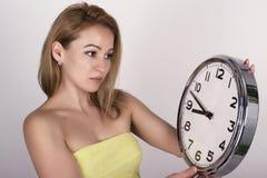 Härlig ung kvinna som ser en retro klocka för stor silver att hon rymmer Royaltyfria Bilder