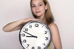 Härlig ung kvinna som ser en retro klocka för stor silver att hon rymmer Royaltyfri Foto