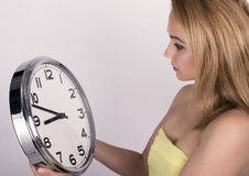 Härlig ung kvinna som ser en retro klocka för stor silver att hon rymmer Arkivfoto
