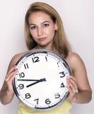 Härlig ung kvinna som ser en retro klocka för stor silver att hon rymmer Arkivfoton