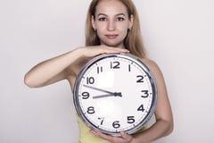 Härlig ung kvinna som ser en retro klocka för stor silver att hon rymmer Royaltyfri Fotografi