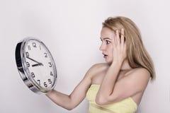 Härlig ung kvinna som ser en retro klocka för stor silver att hon rymmer Arkivbild