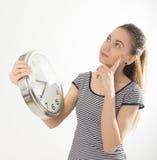 Härlig ung kvinna som ser en stor silver Arkivbild