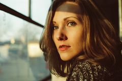 Härlig ung kvinna som ser fönstret under solnedgång royaltyfri foto