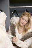 Härlig ung kvinna som ser prislappen av bröllopsklänningen i brud- lager royaltyfri bild