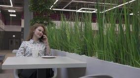 Härlig ung kvinna som sitter på en tabell i ett kafé som talar på telefonen lager videofilmer