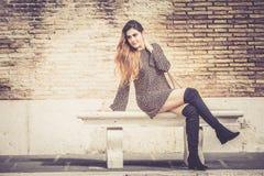 Härlig ung kvinna som sitter utomhus på en bänk Trendigt och sinnligt Royaltyfri Fotografi