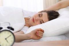Härlig ung kvinna som sover, medan ligga i hennes säng Begreppet av angenämt och vilar återinsättandet för aktivt liv royaltyfri fotografi