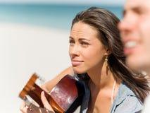 Härlig ung kvinna som spelar gitarren på stranden royaltyfria bilder