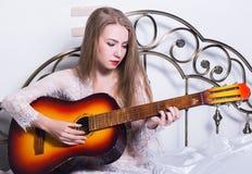 Härlig ung kvinna som spelar musik på en säng med lycka och gitarren arkivbild