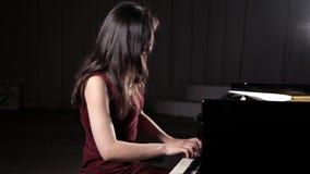 Härlig ung kvinna som spelar pianot i konserthallen, repetition stock video