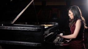 Härlig ung kvinna som spelar pianot i konserthallen, repetition arkivfilmer